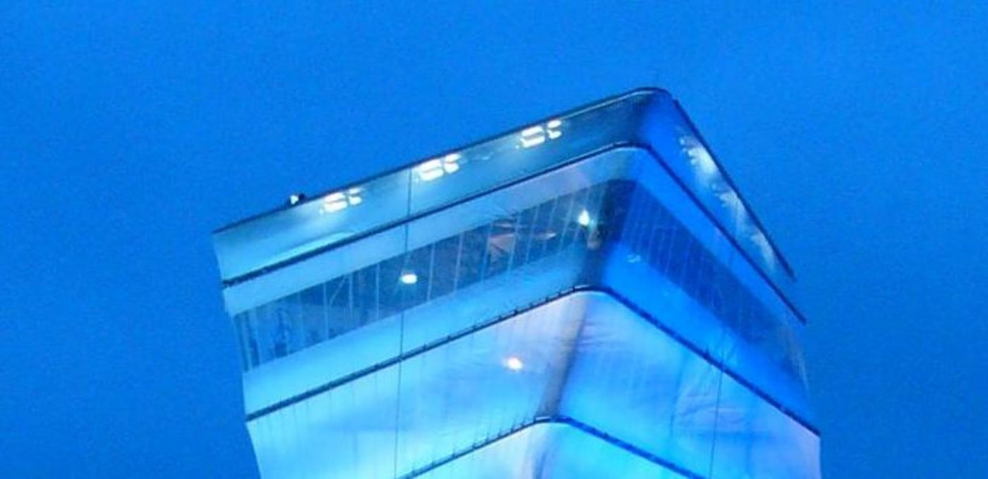 Photo: BBI Infotower – nightly view of the tower illuminated in turquoise whose triangular ground plan continuously twists upwards