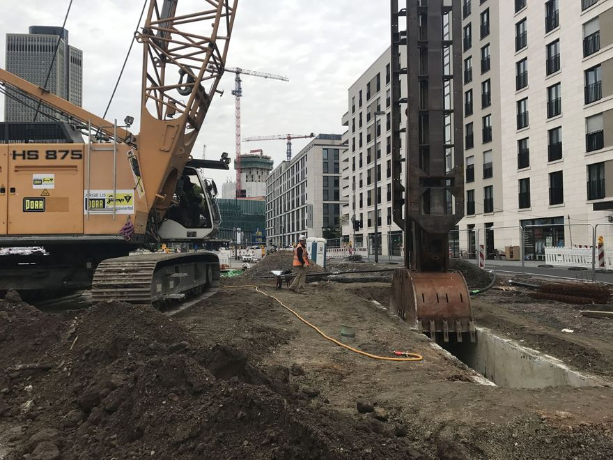 Photo: A slurry trench wall gripper is excavating soil to prepare the slurry trench wall. A construction worker is monitoring the work. In the background you can see the dense inner city development in Frankfurt.