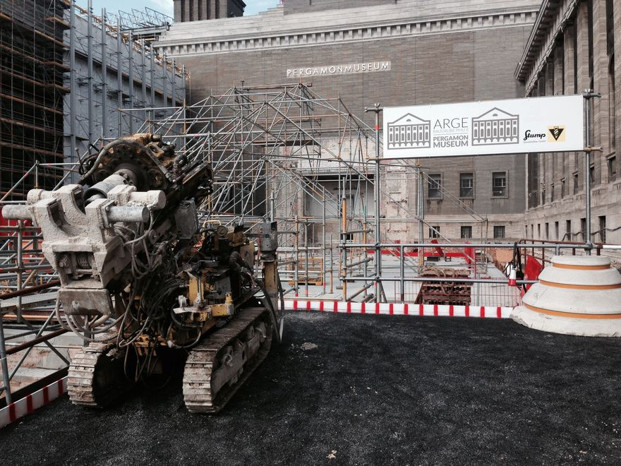 Photos: Construction site in the Pergamon museum. A pile drill is ready for use in the foreground. There is a large amount of scaffolding in the background.