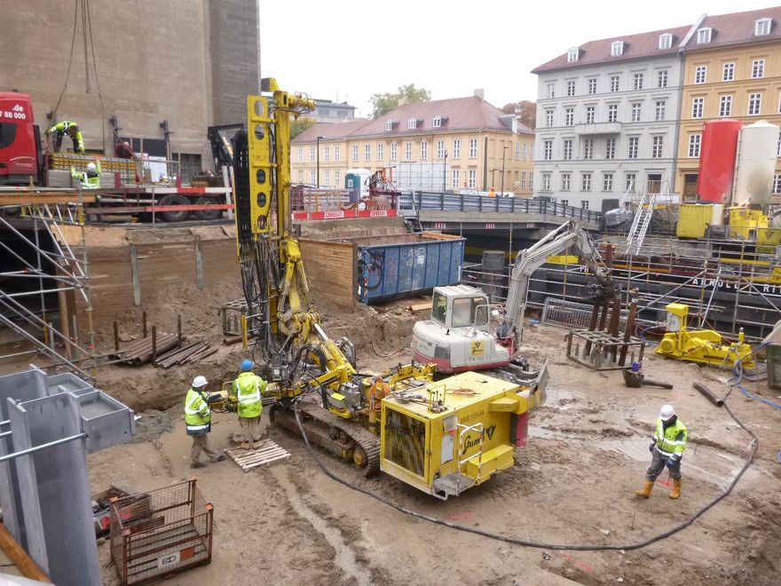 Photo: The excavation with numerous smaller construction devices. A pile is bored in the foreground. Materials are moved from one position to another in the background.