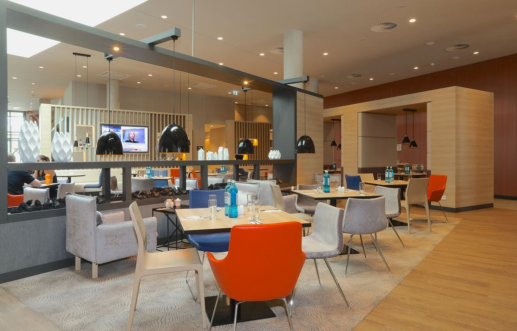 Photo: The restaurant area with square tables, black table lamps and different colored chairs and different materials wood, velvet and leather in gray, blue and orange. Open shelving and design elements separate the groups of tables.