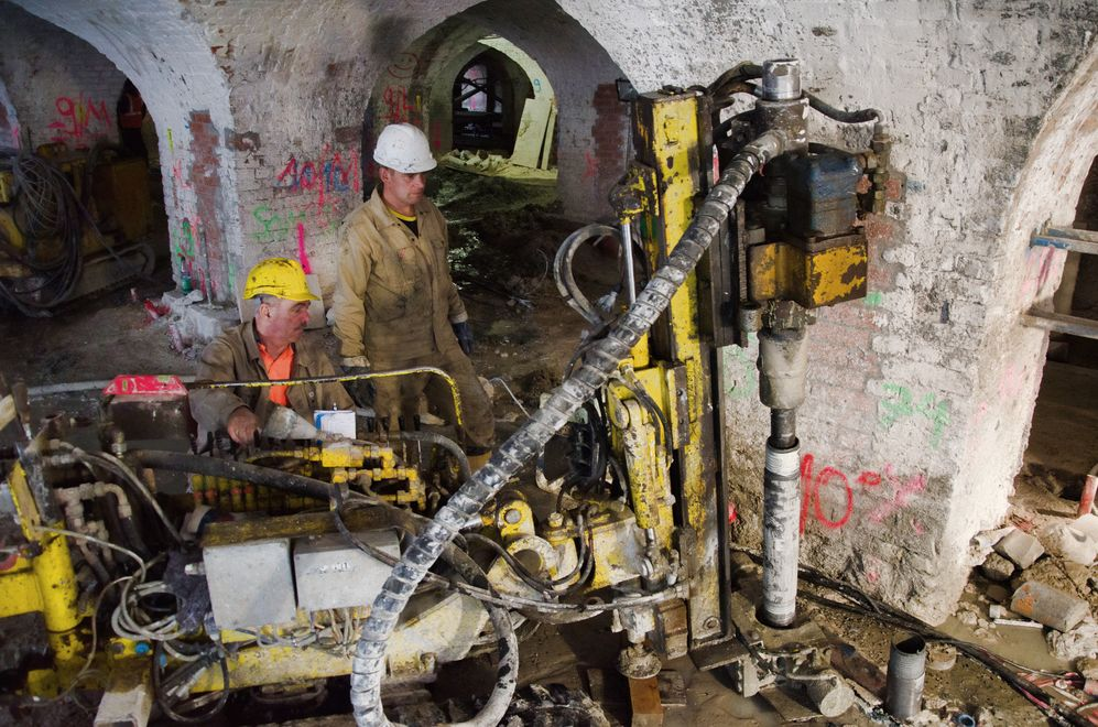 Photo: Two male employees operate a construction machine, which inserts cement into a small hole, in the arches of the basement.