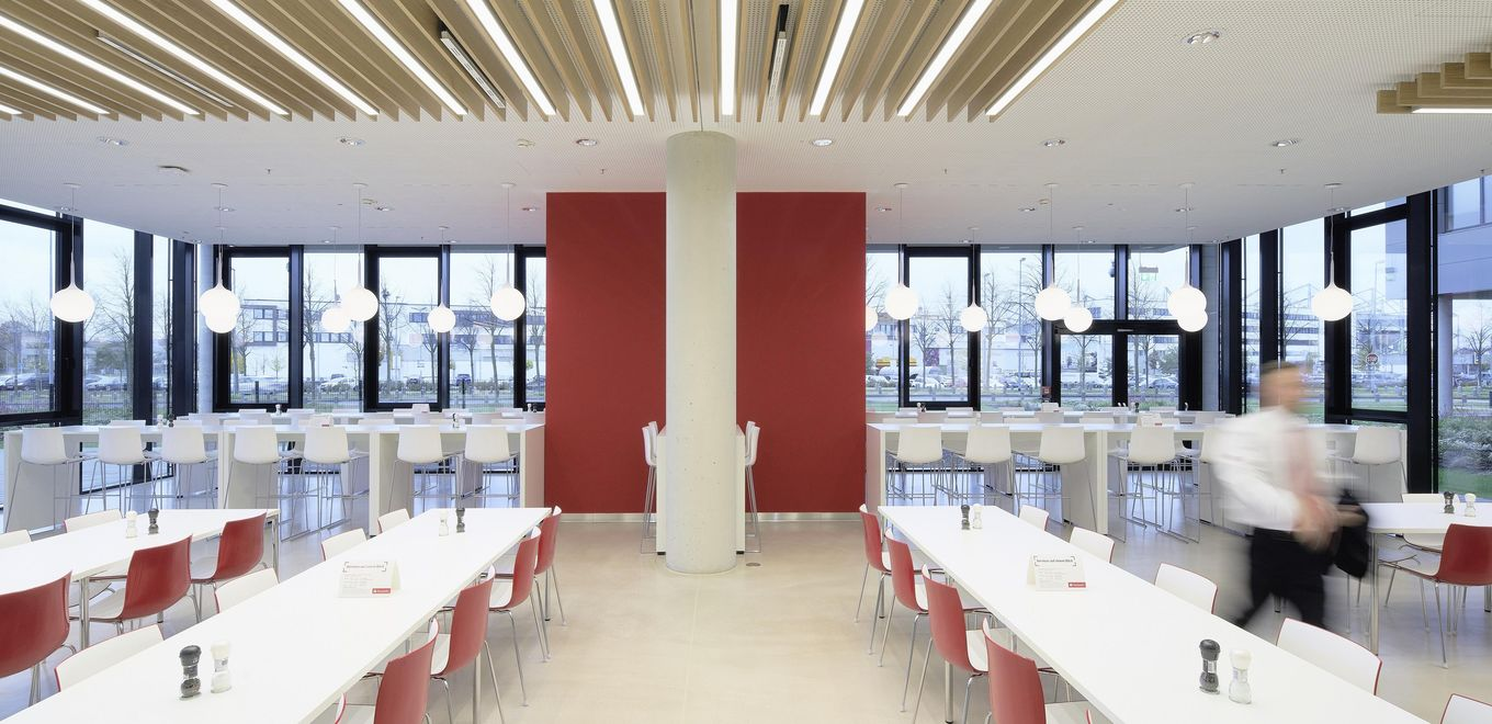 Photo: Santander Group office building: Elegant, white and dark red canteen area with continuous, structured window strip.